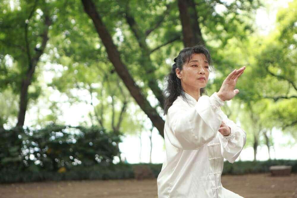 vrouw doet aan tai chi in het bos