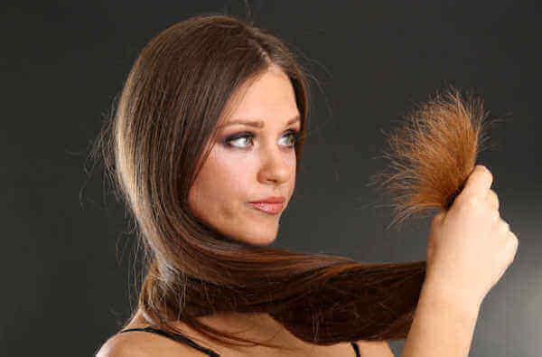 vrouw bekijkt haar droge haren