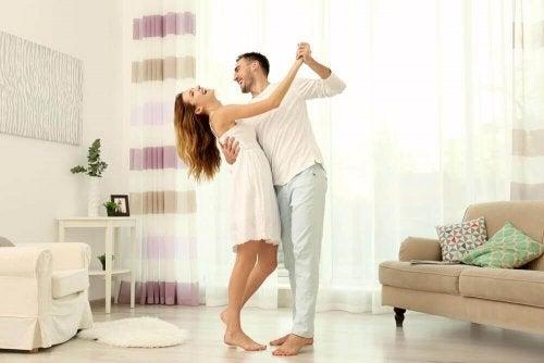 Man en vrouw dansen in de woonkamer