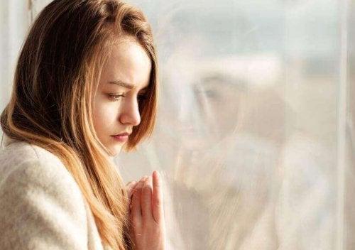 Eenzame vrouw leunt tegen het raam