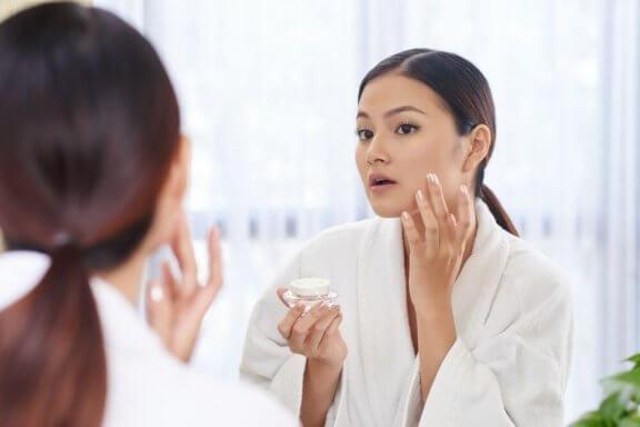 Vrouw brengt crème aan op haar gezicht