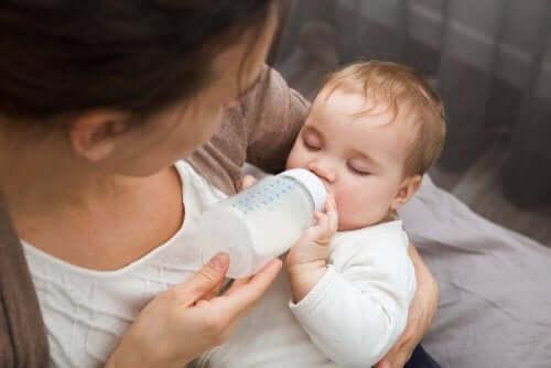Een baby krijgt de fles van de moeder
