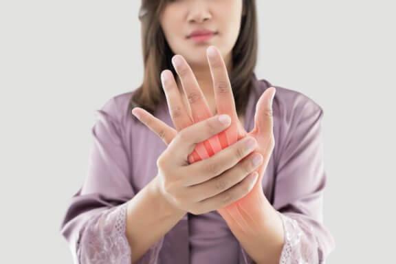 Vrouw heeft pijn in de gewrichten van haar hand
