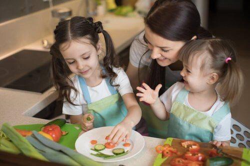 Moeder en meisjes die samen groenten snijden