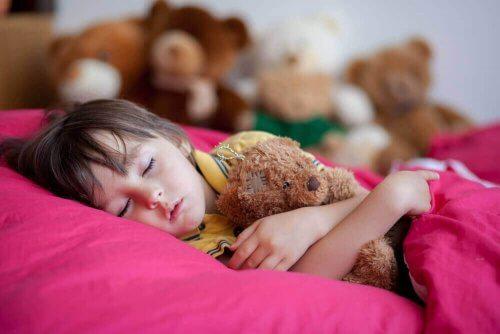 kind slaapt met een knuffelbeer