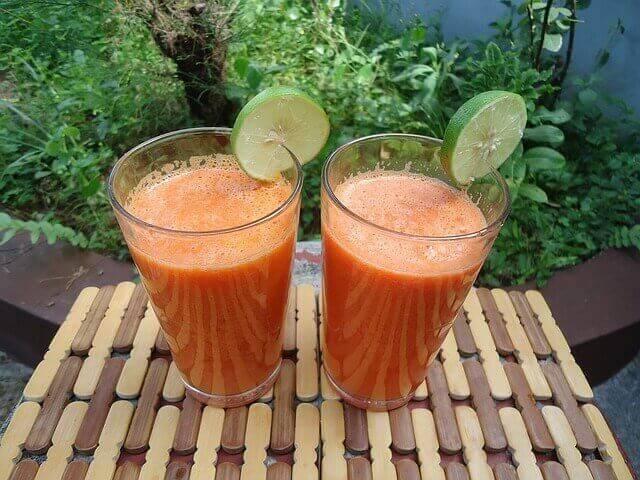twee glazen met een oranje smoothie
