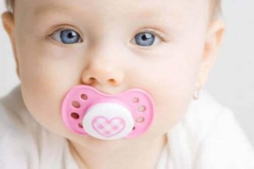 Een baby met een speen in de mond