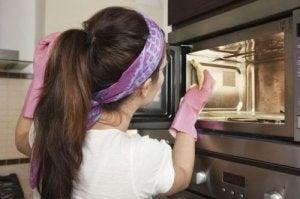 Vrouw die magnetron schoonmaakt