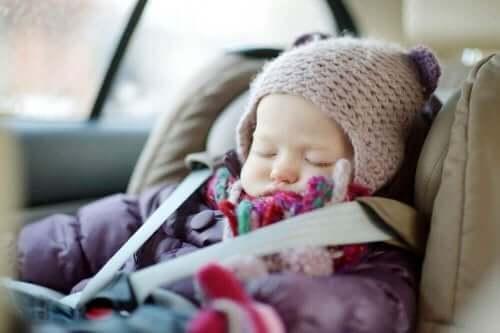 Slapende baby in een autozitje