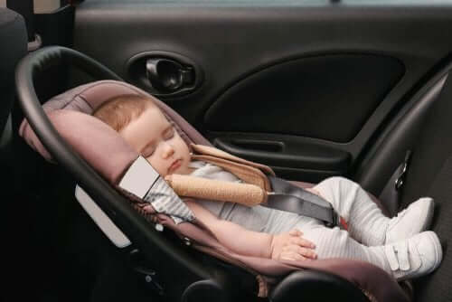 Baby ligt in een autozitje te slapen