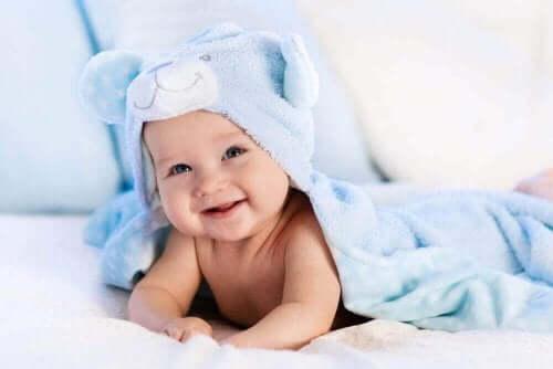 Een lachende baby onder een deken
