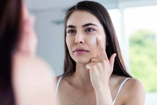 Een vrouw brengt crème aan op haar gezicht