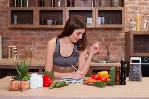 Vrouw schrijft een recept op aan de keukentafel