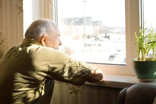 depressieve oude man kijkt uit het raam