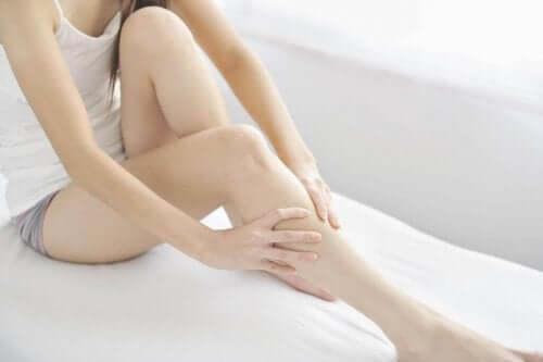 Vrouw die haar benen masseert