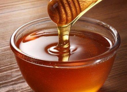 Een kom honing om gastritis te verlichten
