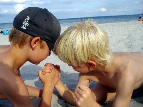 Jongens doen een krachtmeting op het strand