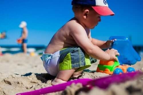 Jongen op het strand met speelgoedauto