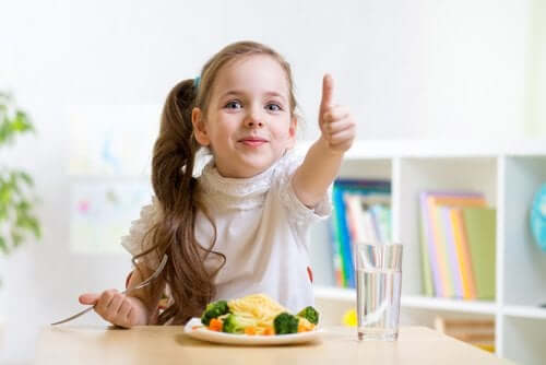 Meisje is blij met haar bord met groente