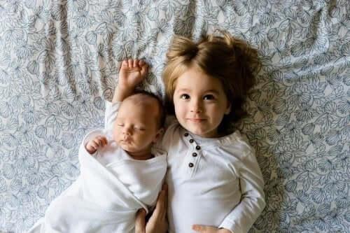 Een baby en een peuter die in bed liggen