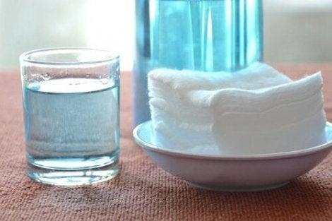 Glas met waterstofperoxide en handdoeken