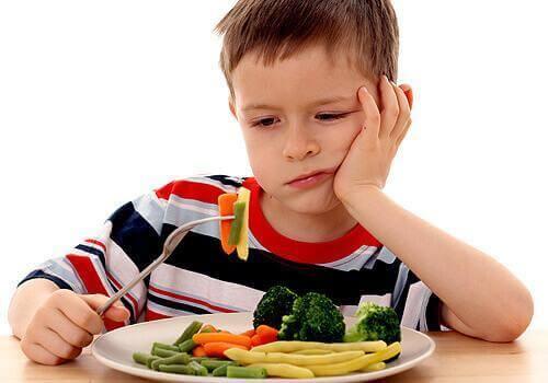 Een kind met groenten op zijn vork en een ontevreden uitdrukking