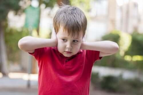 Jongetje houdt zijn handen tegen zijn oren