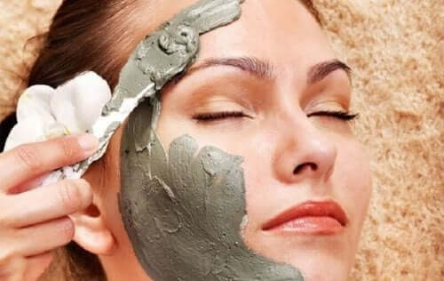 Een vrouw brengt een kleimasker aan op haar gezicht
