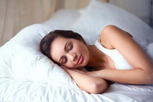 Een vrouw ligt in bed te slapen