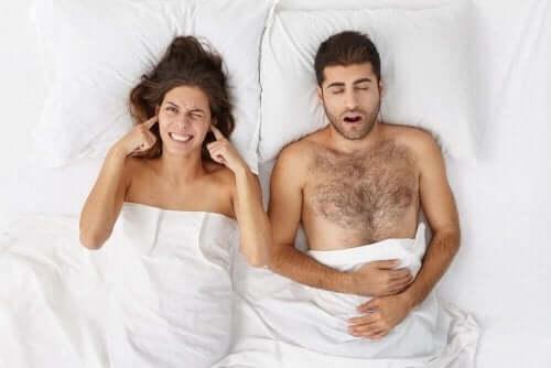 Een man snurkt en vrouw houdt vingers in haar oren