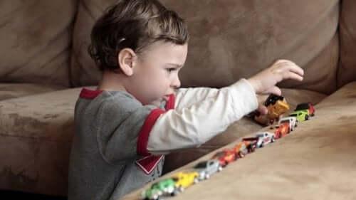 Een kind zet speelgoedauto's op een rij