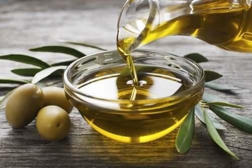 Met een flesje olijfolie in een schaaltje gieten