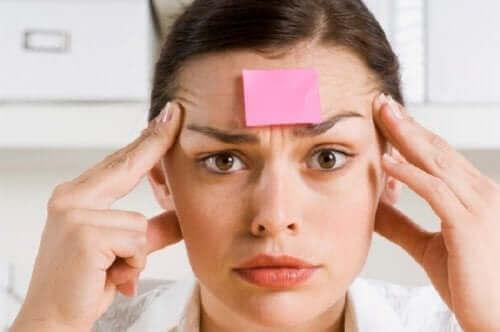 Een vrouw met een post-it op haar voorhoofd
