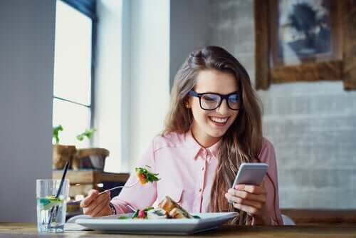 Een vrouw eet terwijl ze afgeleid is door haar telefoon