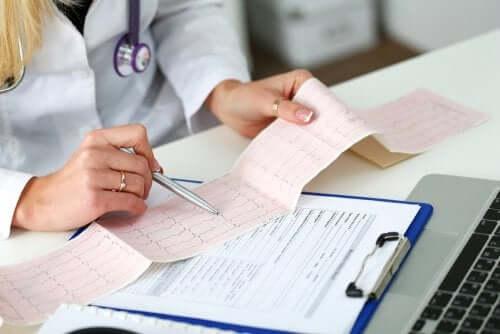 Een arts kijkt naar een ECG uitdraai