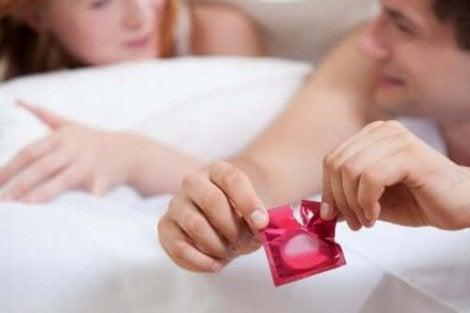Een man scheurt een condoomverpakking open