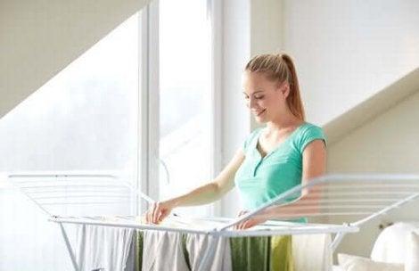 Een vrouw hangt haar kleding aan het droogrek