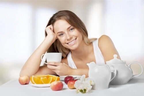 Een vrouw drinkt thee en eet fruit