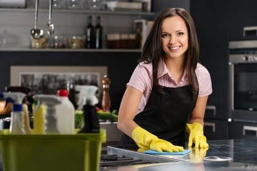 Een vrouw maakt het aanrecht schoon