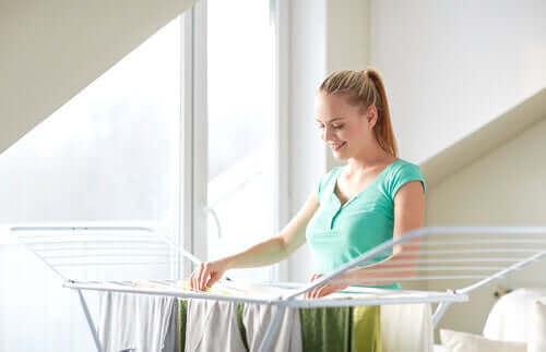 Een vrouw hangt de was op aan een droogrek