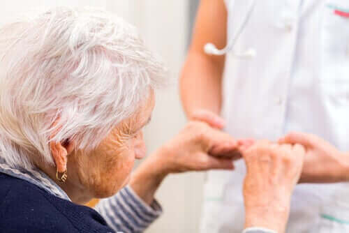 Een oudere vrouw pakt de handen van een zuster