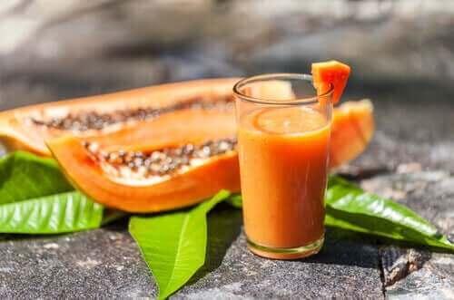 Papajasap in een glas met twee stukken papaja