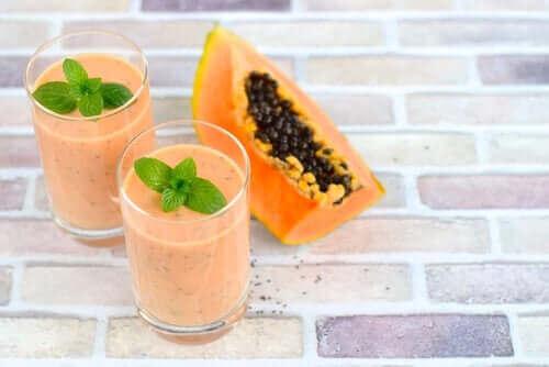 Papajasmoorthies in glazen met een stuk papaja