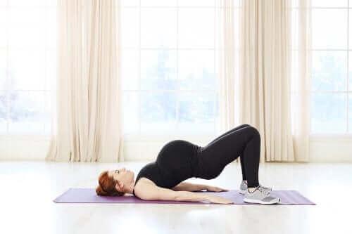 Een zwangere vrouw doet aan pilates
