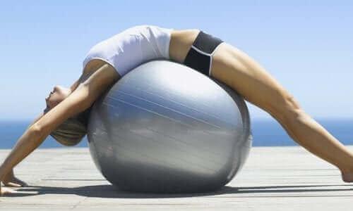 Een vrouw ligt op een pilatesbal