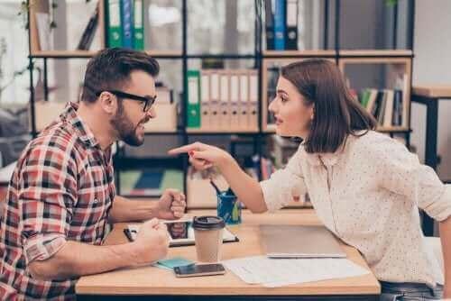 Een man en een vrouw maken ruzie over een bureau
