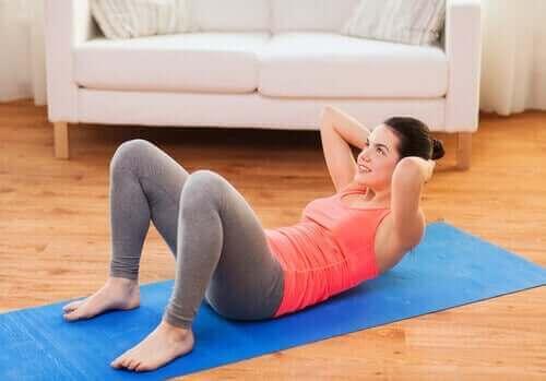 Een vrouw doet buikspieroefeningen op een yogamat
