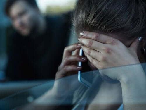 Een vrouw is aan de telefoon met haar hand voor haar gezicht