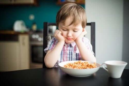 Jongen zit bij zijn bord eten te mokken