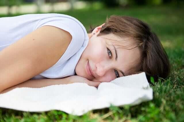 Vrouw ligt te relaxen op het gras